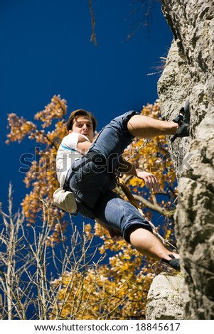 Rock Climber hanging in the cliff looking down - stock photo
