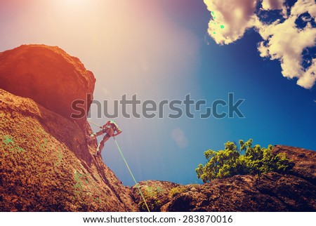 Rock climber on a cliff against the sky background. Vintage colors - stock photo