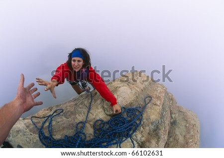 Rock climber on the summit reaching for a helping-hand from her partner. - stock photo
