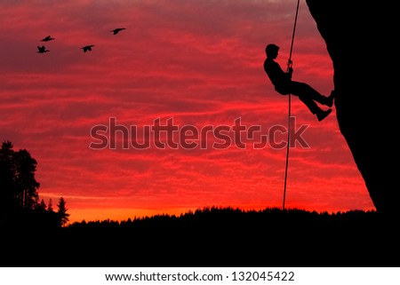 Rock Climber Rappelling Silhouette - stock photo