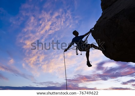 Rock climber rappells from the summit after a successful ascent. - stock photo