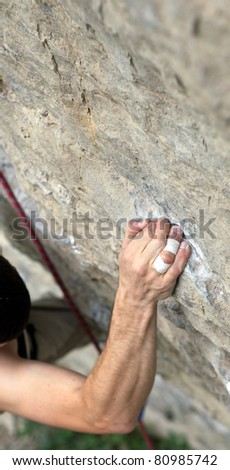 Rock climber's hand grasping handhold on cliff - stock photo