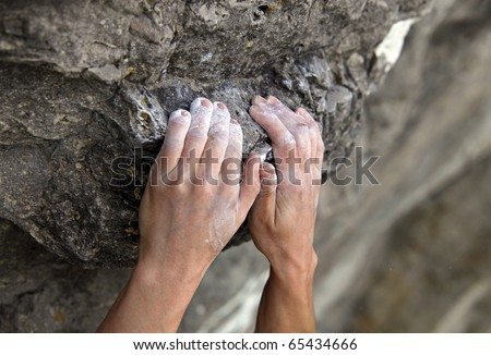 Rock climber's hands on handhold - stock photo