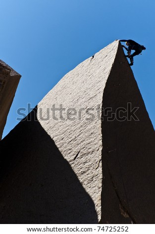 Rock climber struggles for his next grip on a challenging ascent.
