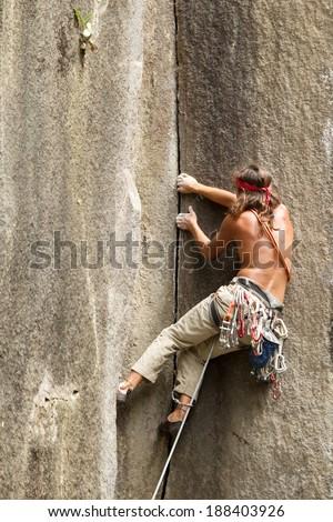 Rock climbing on a perfect vertical plane rock - stock photo