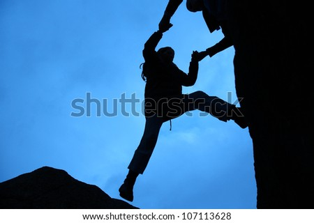 Rock climbing silhouette, gets a helping hand to get up