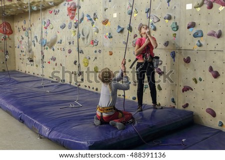 Rock climbing. Two girls in indoor climbing center, preparing to rise up.