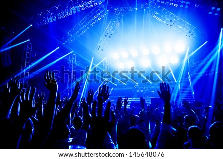 Rock concert, crowd of young people enjoying night performance, raised up and clapping hands, dance club, bright blue lights, music entertainment - stock photo