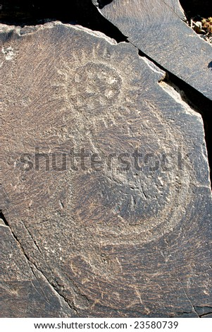 Rock drawings with ancient petroglyphic image of an ancient deity. Area Tamgaly - stock photo