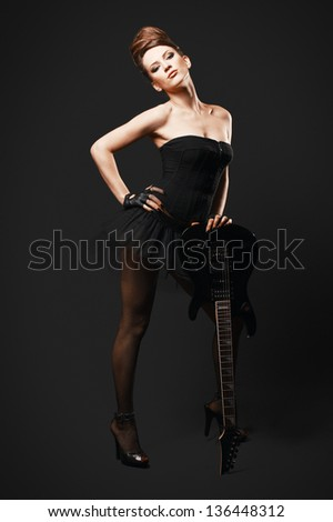 Rock female with guitar over dark background. - stock photo