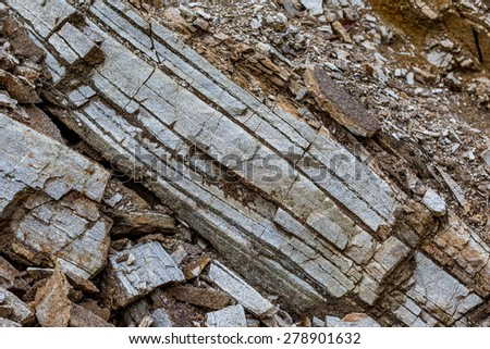 Rock formation. Geology. Layers of gray stones and dirt shaped in diagonal lines. - stock photo
