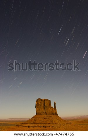 Rock formation in Monument Valley Tribal Park with star trails - stock photo