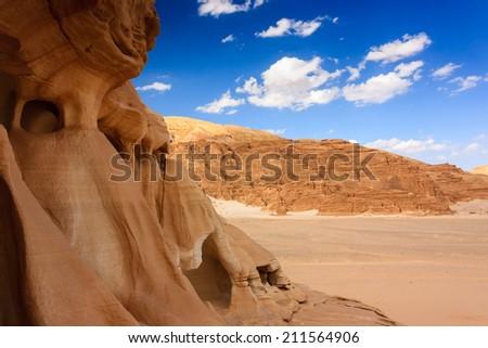 Rock formations in an empty, sandy desert - stock photo
