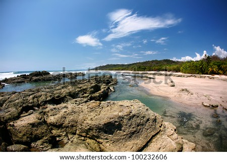 Rock formations in the ocean with waves approaching and blue sky near sandy beach and forest - stock photo