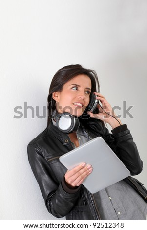 Rock girl listening to music with electronic tablet - stock photo