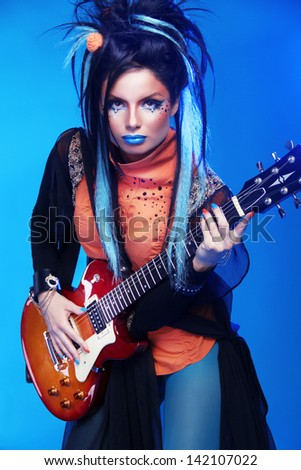 Rock Girl Posing With Electric Guitar Playing Hard Isolated On Blue Background
