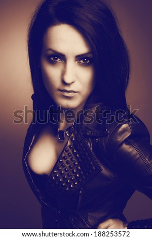 Rock girl, wearing leather jacket, sexy cleavage and eyes fixed on the glass. Vintage portrait.