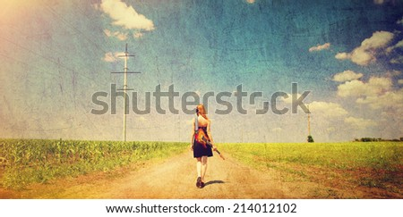 Rock girl with guitar at countryside. - stock photo
