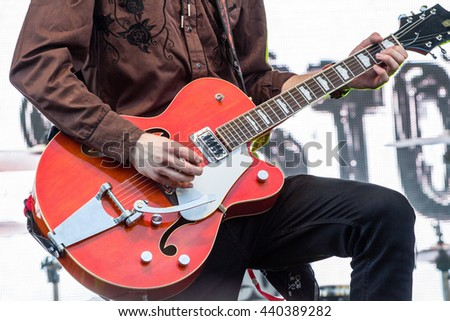 Rock guitar solo on red guitar at rock concert. - stock photo