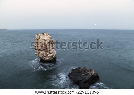 Rock in sea near to the coast - stock photo