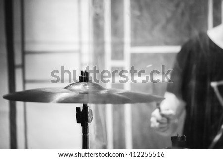 Rock music blurred background, drummer plays on cymbal. Black and white photo - stock photo