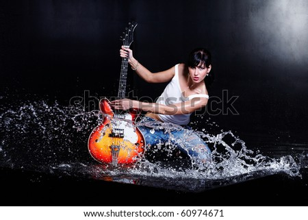 Rock-n-roll girl playing a guitar in water on black - stock photo