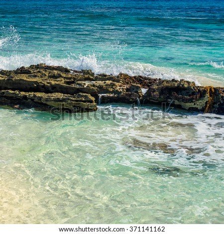 Rock on tropical beach and clear water of the turquoise sea. Caribbean Sea scenery in Playa del Carmen, Yucatan, Mexico.  - stock photo