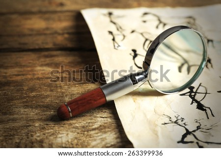 Rock paintings with magnifier on paper on wooden table close up - stock photo