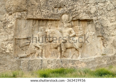 Rock relief cuted into the cliff. Naqsh-e Rustam, an ancient necropolis in Pars Province, Iran - stock photo