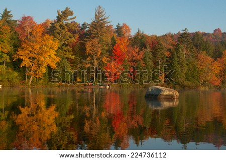 Rock sits out in the calm lake surrounded by the beauty of the autumn colors - stock photo