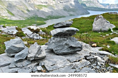 Rock stack with mountain and lake background - stock photo