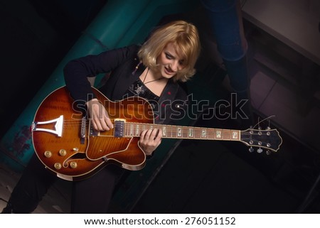 Rock star playing guitar on industrial background. Low key - stock photo