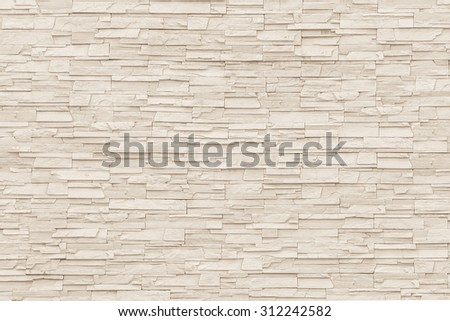 Rock stone brick tile wall aged texture detailed pattern background in light sepia cream brown color tone: Grunge ancient rustic limestone patterned backdrop for decoration in creme toned colour    - stock photo
