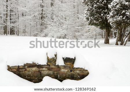 Rock wall of a bridge covered in snow and snow covered trees in winter - stock photo