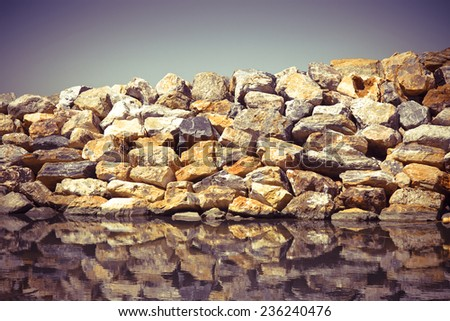 Rock wall protection from the waves - concept image - stock photo