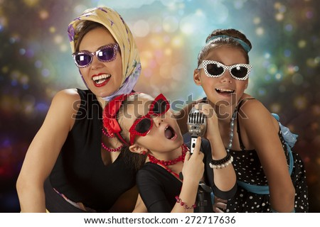 Rockabilly woman with her tow daughters having fun posing with vintage microphone in 1950s style clothing  - stock photo