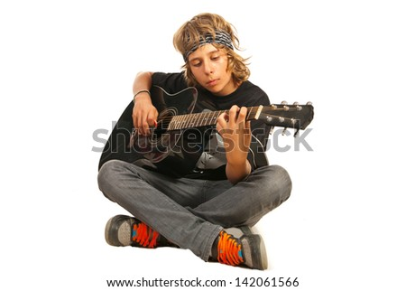 Rocker teen with bandana playing accoustic guitar isolated on white background - stock photo