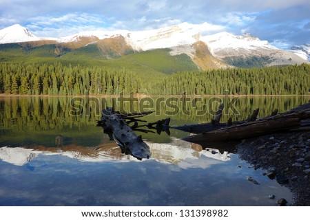Rockies mountain range reflecting in Maligne lake, Jasper national park - stock photo