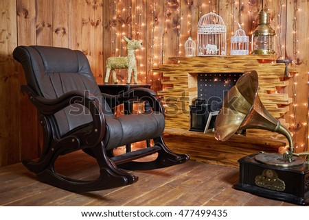 Merveilleux Rocking Chair And Gramophone Near Fireplace In Room With Wooden Walls And  Floor.