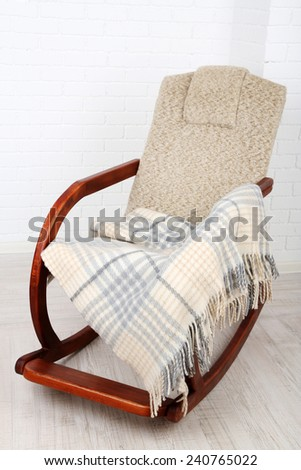 Rocking chair covered with plaid on wooden floor near the brick wall background - stock photo