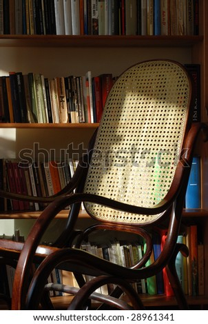 Rocking chair in home library - stock photo