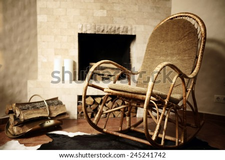 Rocking chair near the fireplace. - stock photo