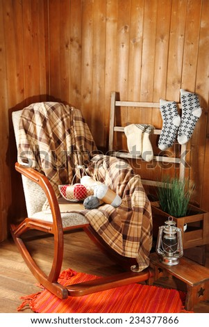 Rocking chair with plaid and yarn for knitting near wooden wall - stock photo