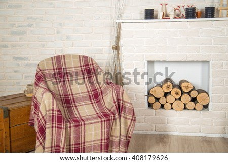 Rocking chair with plaid near the fireplace. - stock photo
