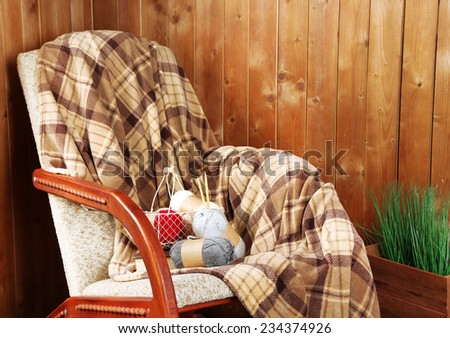 Rocking chair with plaid near wooden wall - stock photo