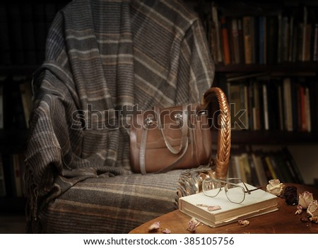 Rocking chair with plaid on the background of bookshelves