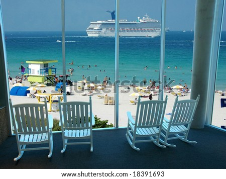 Rocking chairs by the window overlooking a scenic beach resort with a cruise ship passing by - stock photo
