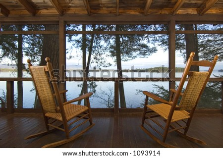 Rocking chairs on a porch looking out over the lake. - stock photo