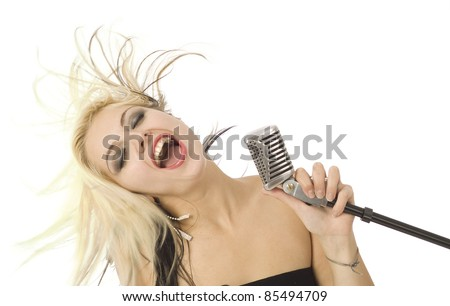 Rocking singer with wild hair and microphone - stock photo