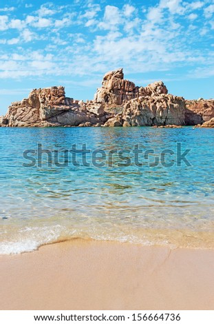 rocks and blue sea under a cloudy sky